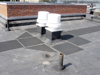 An EPDM membrane is fully adhered to a coverboard over the primary insulation. The walk pads are a protective layer for foot traffic and tools or equipment placed on the roof during maintenance of the mechanical vents.