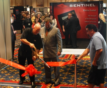 Troy Bix, vice president of Inside Self-Storage, looks on as Jon Reddick, president of Sentinel Systems Corp., cuts the ceremonial ribbon at the opening of the ISS Exhibit Hall on April 3.